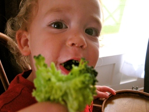 A kid truly happy to eat broccoli!
