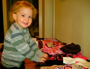 Nash smiles with a pile of new clothes for Baby Opi! It's going to be so much fun to dress a little girl!